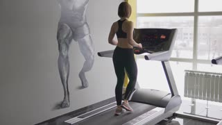 An adult woman wants to bring her body in shape before the summer beach season. The sportswoman warms up her body on the treadmill before power training with the trainer