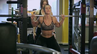 An athlete in an elastic suit squats in a sports club. The coach carefully monitors the correctness of the exercise to ensure that the bar with the load does not fall on the client.