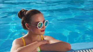 An attractive and young woman who wears a swimsuit and sunglasses enjoys cool water in the pool, she smiles this sunny day in her summer vacation