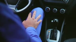 Arab man in blue suit sitting in the car on the driver seat. He waiting for someone and looks very impatient. Close up view inside the car