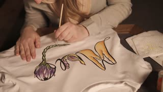 Artist is painting shirt by acrylic dyes. She is covering fabric by beautiful floral ornament, handmade of clothing