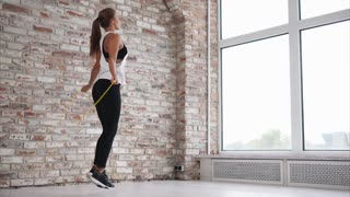 Athletic woman is jumping rope wearing sportswear indoor. Sportswoman is training hard at the gym.