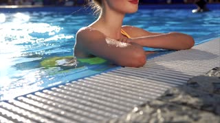 Attractive and young woman resting in pool, lady enjoying cool water on a sunny day, smiling and enjoying on a day off, the sun helps getting sunburn