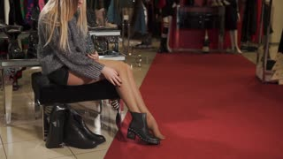 Attractive blonde girl is trying on brand new leather shoes. She is sitting on a comfy chair looking at the shoes.