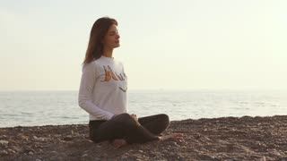 Attractive brunette girl is sitting on a seashore crossed legs and breathing fresh air. She is doing meditation and yoga practice, enjoying nature