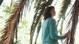 Attractive redhaired woman is standing under palm hiding from sun. Beautiful woman posing on vacationg wearing blue sweater.