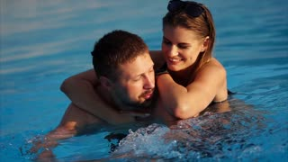Attractive woman wearing black swimsuit is laying on back of his man while he is swimming. They are happily spending time together in the park.