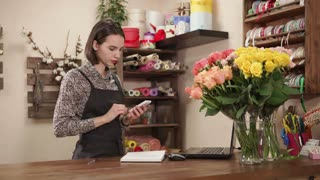 Attractive young woman works in a flower shop alone. She is talking on the smartphone and smiling. Decorations around.