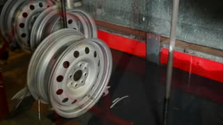 Automatical machine tool is putting metal wheels into liquid. Powder coating is using in the manufacture of steel wheels for cars.