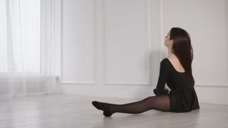 Ballerina is stretching on a floor in a light hall in dancing school. She is sitting and tensing her muscles before class, back view