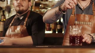 Barmans are working behind bar rack. One man is shaking mixed drinks in shakers, second man is mixing cocktail in a large glass with ice