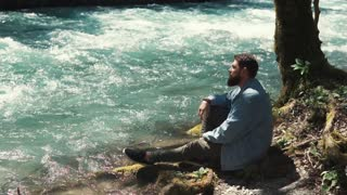 Bearded guy is looking on river flow and turning head. He is sitting lonely in forest after walking and thinking