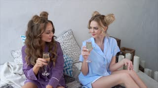 Beautiful and funny friends drink champagne on the bed in the bedroom. Women with stylish hairstyles are dressed in cute pajamas, they clink glasses and drink alcohol champagne.