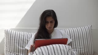 Beautiful brunette woman is surfing the web on big tablet while lying in bed under cover. Reading news and chatting with friends. Using technologies.