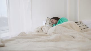 Beautiful brunette woman sleeps in bed under white duvet wearing green pajamas in white room. Bed near the window.