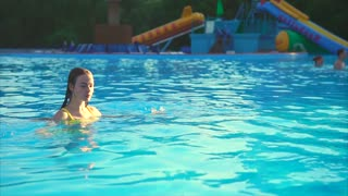 Beautiful fit woman relaxing in the swimming pool. She diving into the water and emerge. Wet hair and attractive look.