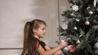 Beautiful little girl in black dress is decorating christmas tree in the room. She is hanging glittery balls on the tree.