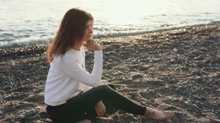 Beautiful lovely woman is posing on the bank barefoot. Woman is sitting on sand on the shore during sunset. Modeling.