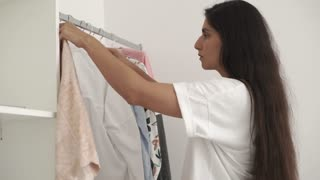 Beautiful mulatto woman is choosing clothes hanging on rack indoor. Woman picking nice blouse for outfit. Stylish clothes.