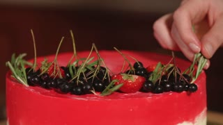 Beautiful shot of a pastry cook doing some final touches decorating the cake. Sweet berries and some herbs on the top of the glaze.