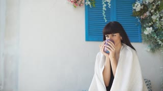 Beautiful woman is sitting on a bed with a blanket on her shoulders and drinking hot tea. She is having a breakfast and smiling.