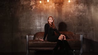 beautiful woman sits on an expensive leather couch, behind her wall in loft style, the lady is in a modern room and posing sitting on the sofa