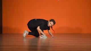 Beautiful young female break dancer against orange wall in studio. Breakdance training and practicing.