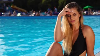 Beautiful young woman with long blond straight hair is sitting near pool in a hotel. She is tanning and touching her hair, many people are on background.
