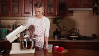 Beuatiful young woman is cooking in her kitchen at home. She is pouring a glass of sugar to other ingredients in the bowl and mixing.