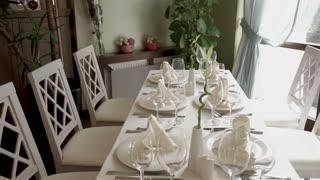 Big table by the window beautifuly served with clean cutlery plates and glasses. Decorated with white napkins.