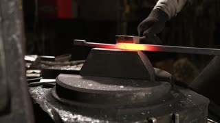 Blacksmith is using hammer machine for shaping metal blank. He is holding beam on a small plate and automatic hammer is hitting on top