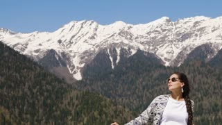 Brunette girl is relaxing outdoors in sunny weather in summer. Mountains with snowy tops and covered forest slopes are in behind her back