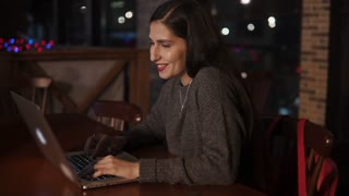 Brunette girl is working with laptop in a cafe in evening. She is sitting alone at table and looking on a display in dark hall