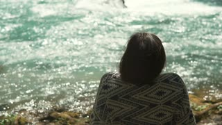 Brunette lady is resting alone in woodland in holidays. She is looking on clear water of river and thinking, back view