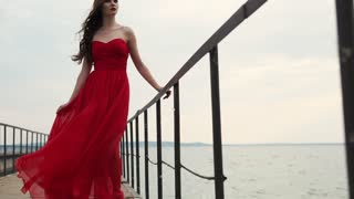 Brunette wearing red chiffon dress is standing on a quay in cloudy summer day. Wind is swaying her skirt, woman is looking in a distance, camera is moving