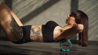 Brunette with sporty fit figure is training in a gym, using fitness roller. She is rolling cylinder by her back, holding hands behind head, in lying position