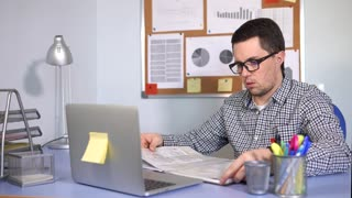 Businessman in his office at work. Man sitting at the desk with laptop and working with papers. He marking important information in book by yellow marker.