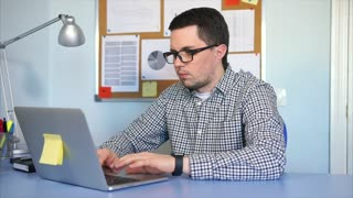 Businessman in shirt and black glasses sitting at desk in office, working on laptop computer.