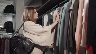 Buyer woman is inspecting costs of modern garments in shop. She is looking on and touching sweaters and price tag