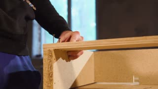 Carpenter is connecting two wooden parts with bolts in a workshop of furniture factory. He is using an electric screwdriver, close-up of hands