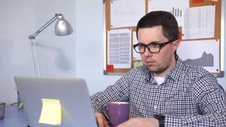 Caucasian casual dressed man working hard in the office at notebook. He drinking coffee while working.