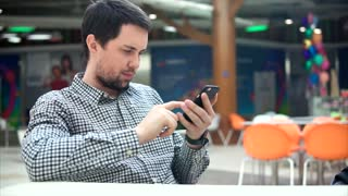 Caucasian man with smartphone in the cafeteria. Electronic technology in everyday life.