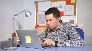 Caucasian man working hard in the office with laptop. Adult man in casual wear.