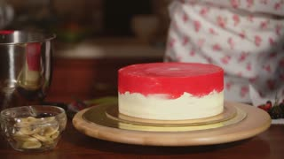 Chef is decorating high sweet cake. Woman is putting on a top a herbs and black rowan, expensive home made creamy cake