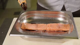 Chef is filling piece of red expensive fish by soya sauce. He is marinating lox before cooking in a professional kitchen in restaurant