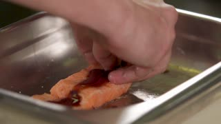 Chef is twisting a fishroll from raw salmon with soya sauce. Close up of male hands in a professional kitchen, preparing authors dish
