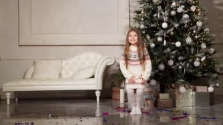 Child girl is joying for onset of Christmas, skipping and waiting to open boxes with gifts. Traditional annually celebrating of New year and Christmas, childrens fest.