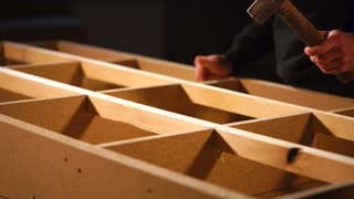 Close-up of assembling of furniture subject in a workshop of joinery. Master is knocking by hummer over wooden beam for installing