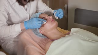 Close up of beauty procedure. Beautician cleaning facial mask off from woman patient. Peeling. Beauty and body skin care.