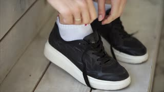 Close-up of hands of young girl, tying laces on sneakers. She is fastenings knot and hiding it inside, athletic shoes for running, training and everyday walking